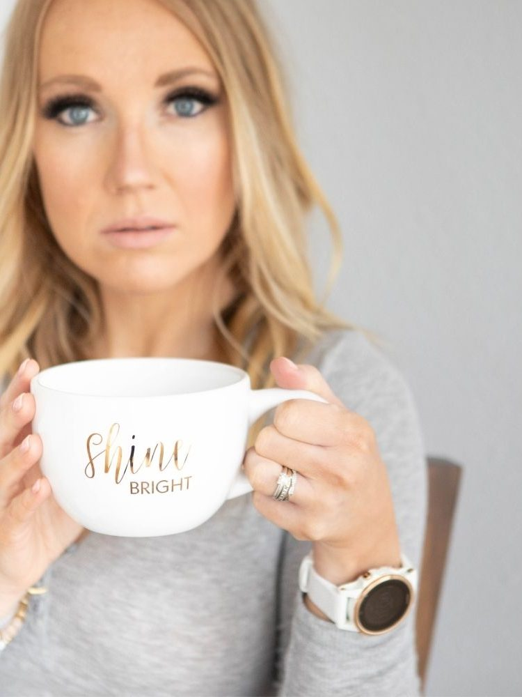 a woman holding a coffee mug that says shine bright