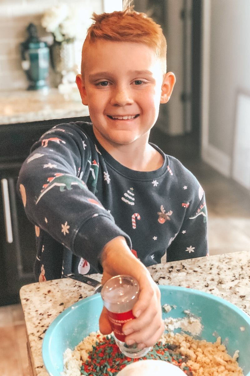 a little boy in christmas pajamas stirring sprinkles and chocolate chips into a bowl. He's smiling at the camera.