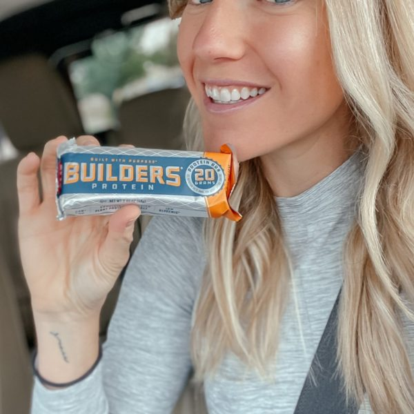 a blonde woman is holding a cliff builder protein bar and smiling at the camera, she's in her car and a seatbelt is strapped across her chest