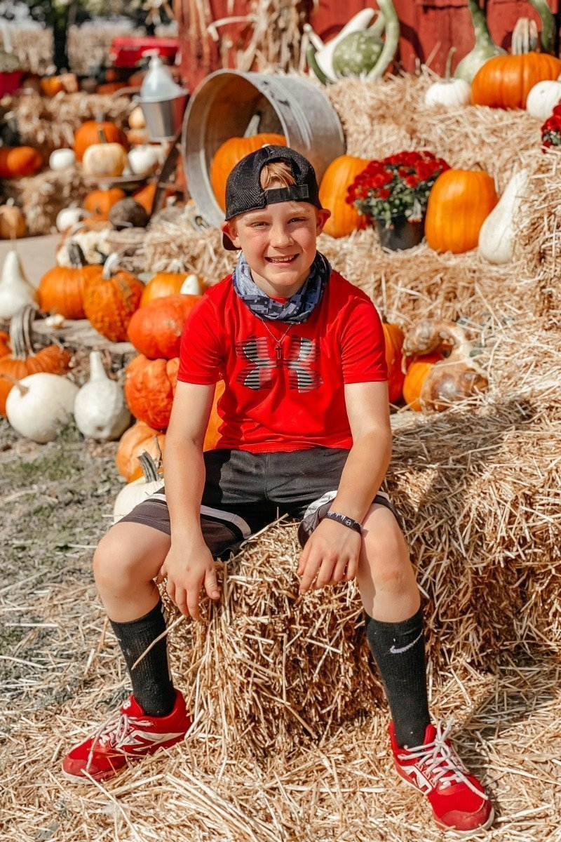 a boy sitting on a haystack in front of a bunch of pumpkins at a pumpkin patch