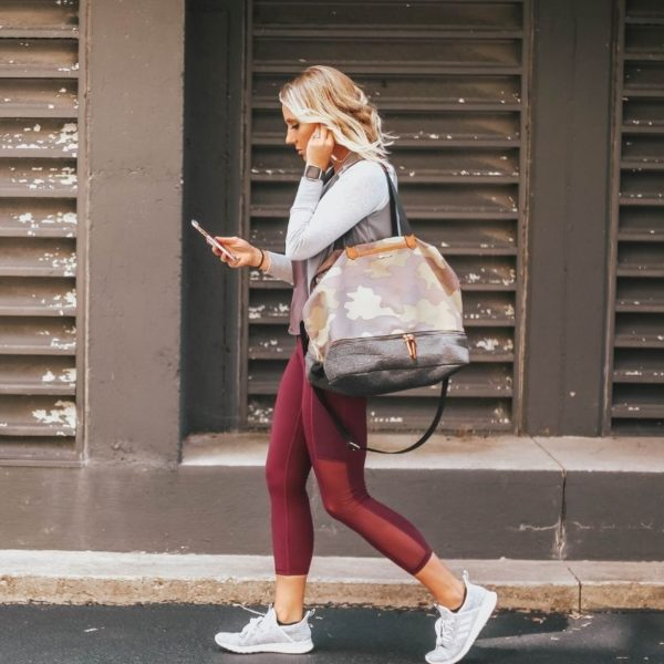 a blonde woman carrying a gym bag is walking down the side of the street staring at her phone
