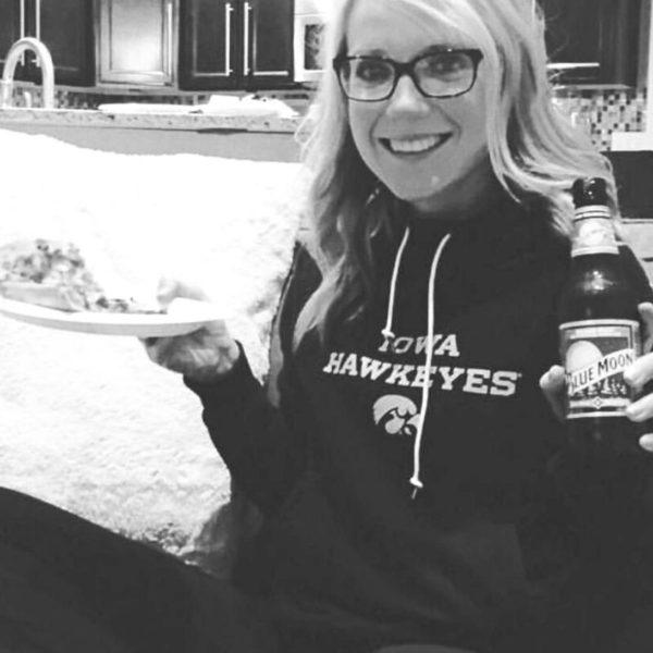 blonde girl sitting on the couch holding a blue moon beer in one hand and a plate of pizza in the other hand. she's smiling.
