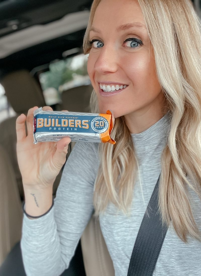 a blonde girl is sitting in her jeep holding up a cliff builder protein bar and smiling