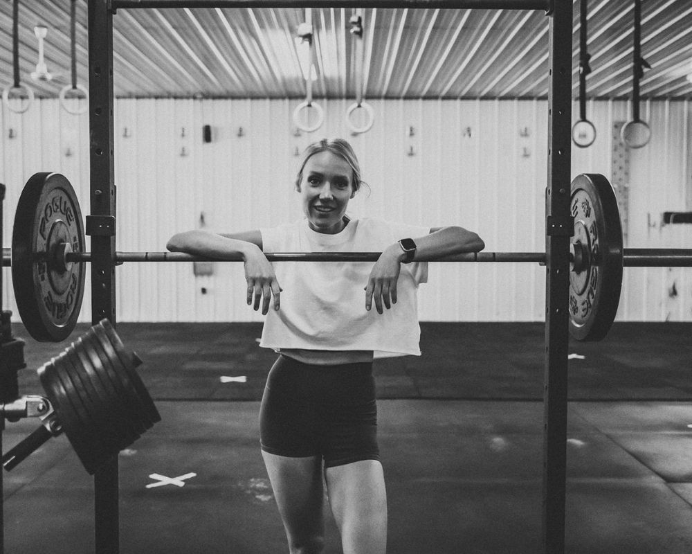 a girl holding onto a barbell at the gym