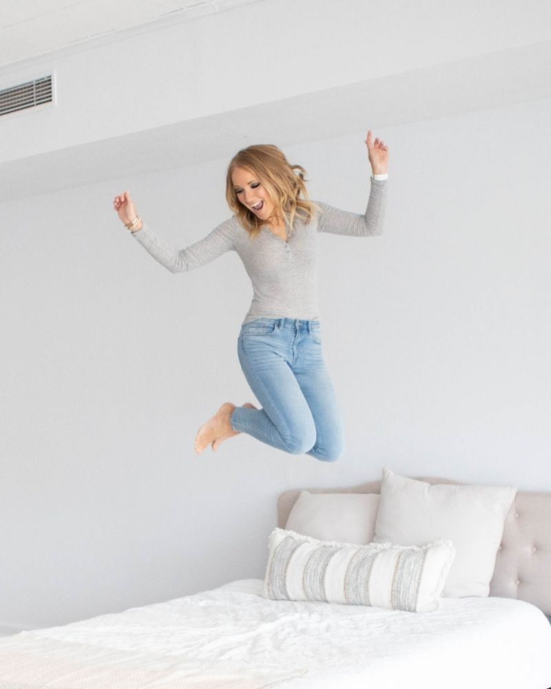 a woman jumping on a bed and she's laughing